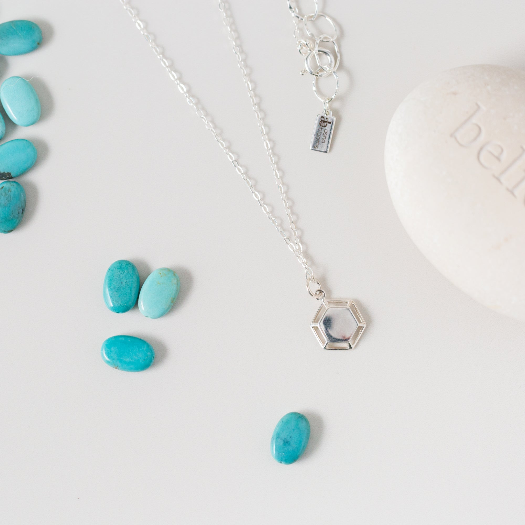 Silver Hexagon Pendant Necklace 'One Day at a Time' Flat Lay with Small Blue Stones Photo by Asha Blooms
