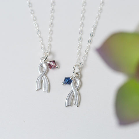 Silver Ribbon Pendant with Pink or Blue Crystal Necklace 'Survivor' Flat Lay with Green Plant Photo by Asha Blooms