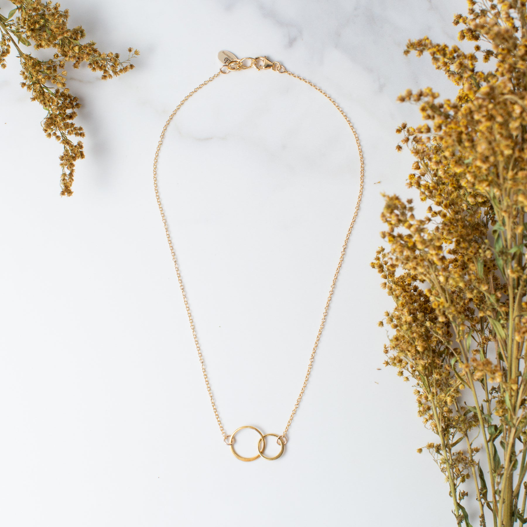 Gold Linked Circles Necklace 'We Are Connected' Flat Lay with Yellow Flowers Photo by Asha Blooms