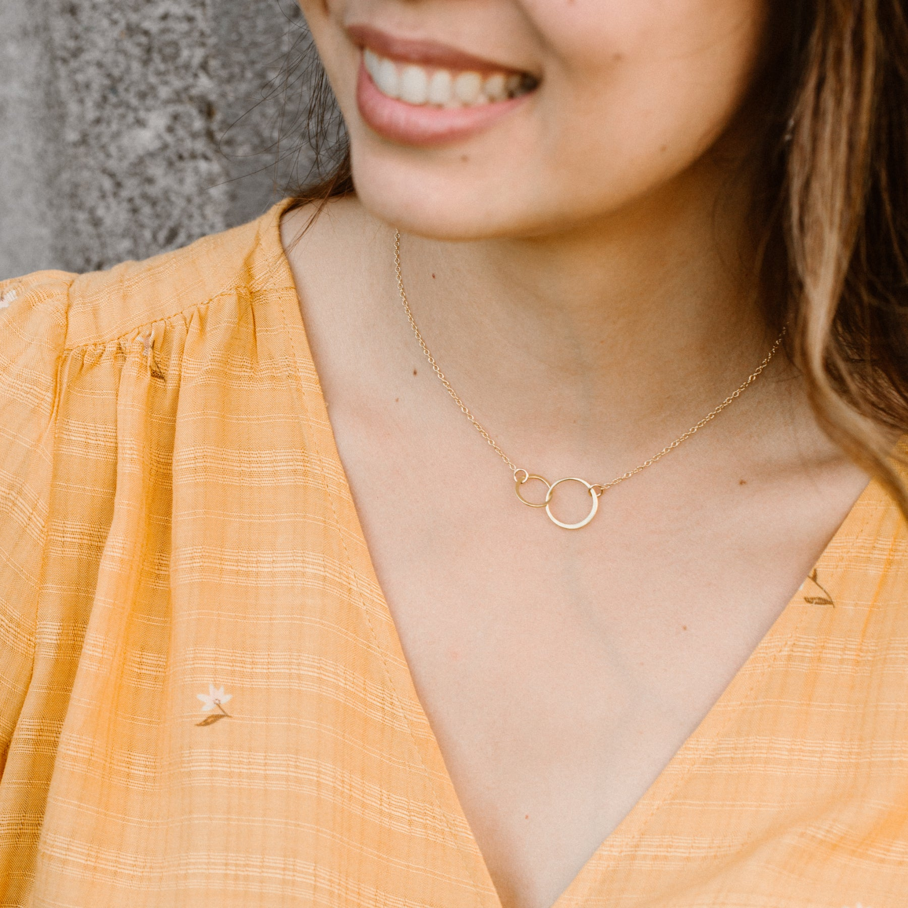 Woman in Orange Shirt Smiling and Wearing Gold Linked Circles Necklace 'We Are Connected' Model Photo by Asha Blooms