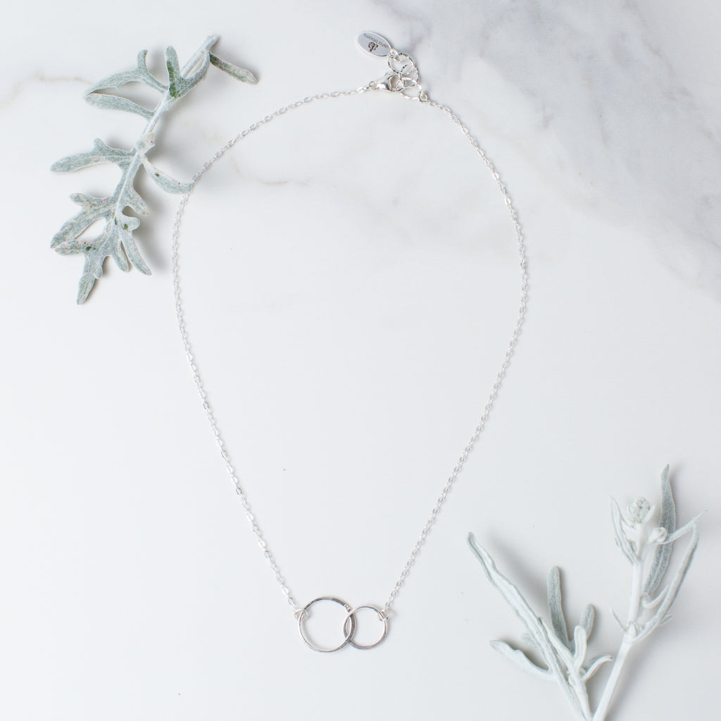 Silver Linked Circles Necklace 'We Are Connected' Flat Lay with White Leaves Photo by Asha Blooms