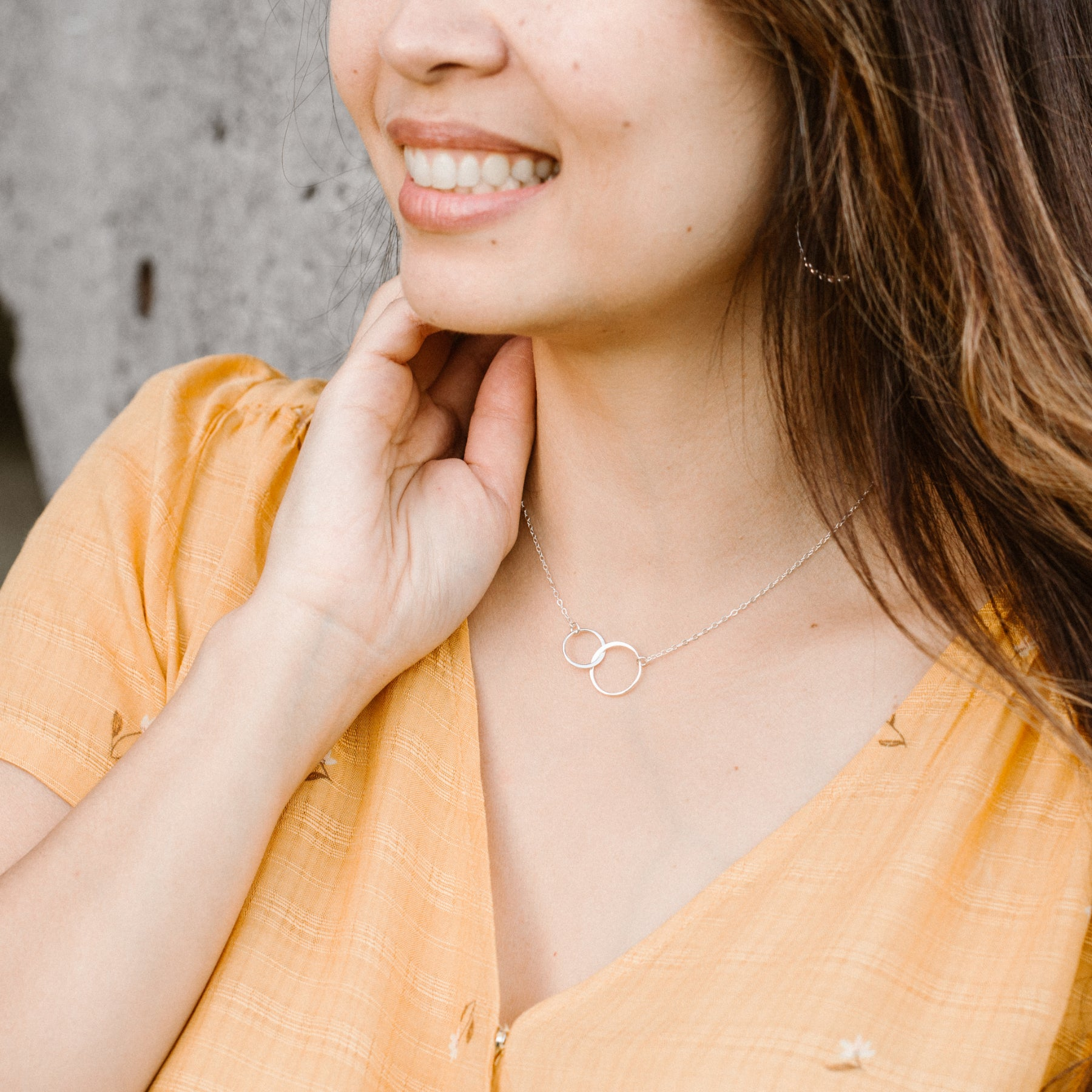 Woman in Orange Shirt Smiling and Wearing Silver Linked Circles Necklace 'We Are Connected' Model Photo by Asha Blooms