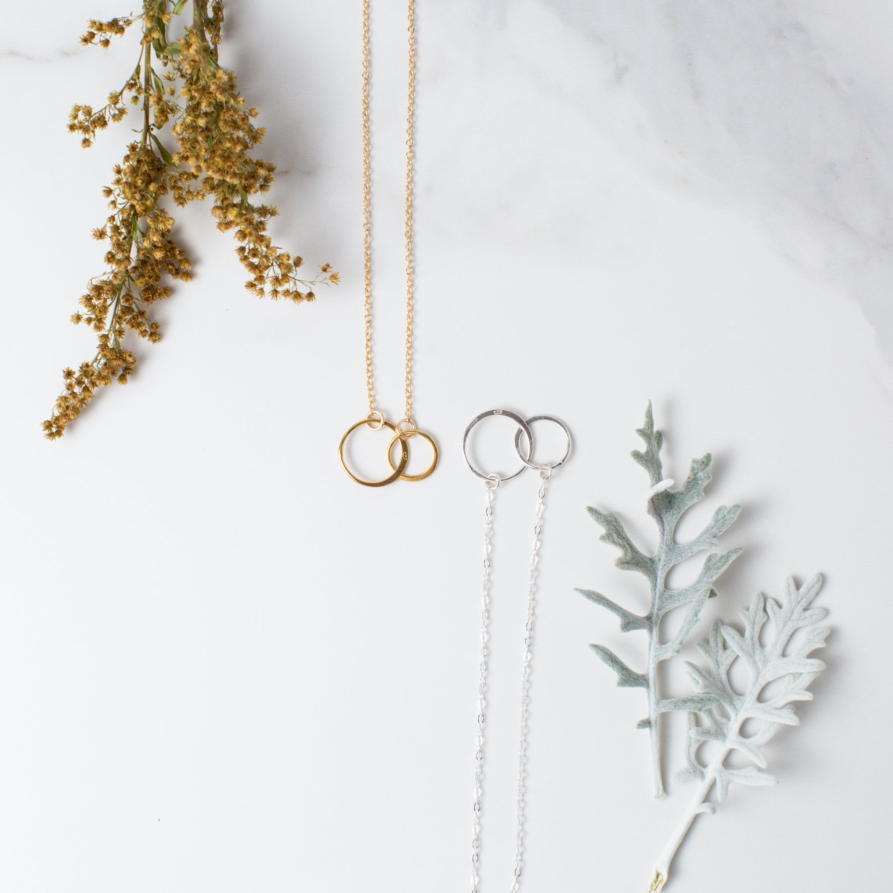 Gold or Silver Linked Circles Necklace 'We Are Connected' Flat Lay with Gold Flowers and White Leaves Photo by Asha Blooms