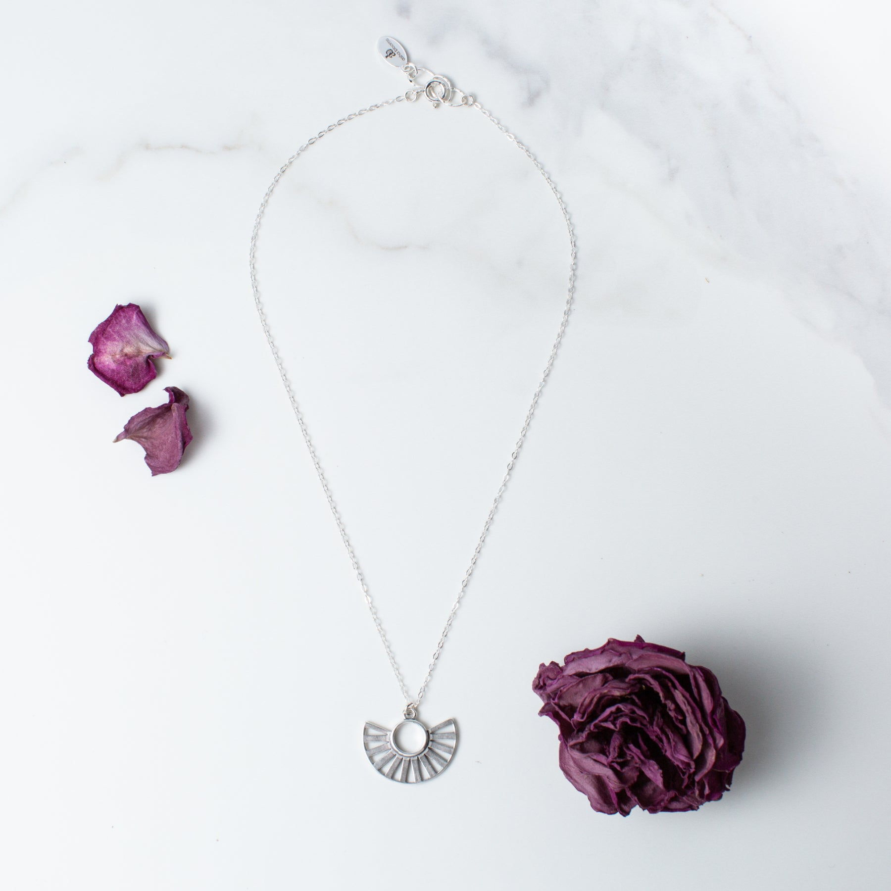 Silver Sun Pendant Necklace 'You Are Becoming' Flat Lay with Purple Flower Petals Photo by Asha Blooms