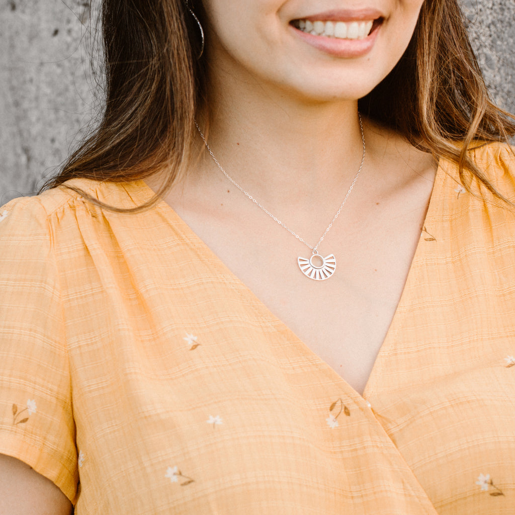 Woman in Orange Shirt Smiling and Wearing Silver Sun Pendant Necklace 'You Are Becoming' Model Photo by Asha Blooms