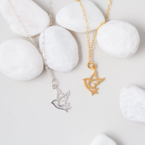 Gold or Silver Bird Pendant Necklace 'You Are Free to Soar' Flat Lay with White Stones Photo by Asha Blooms