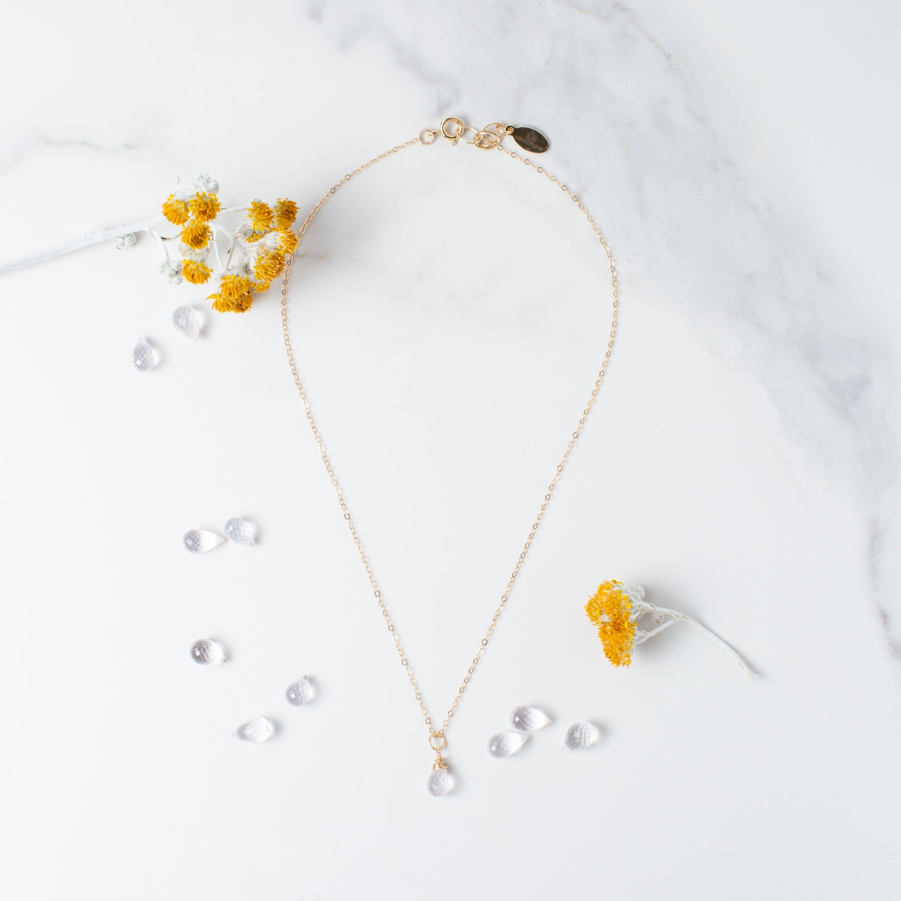 Teardrop-shaped Rose Quartz and Gold Necklace 'You Are Loved' Flat Lay with Yellow Flowers Photo by Asha Blooms