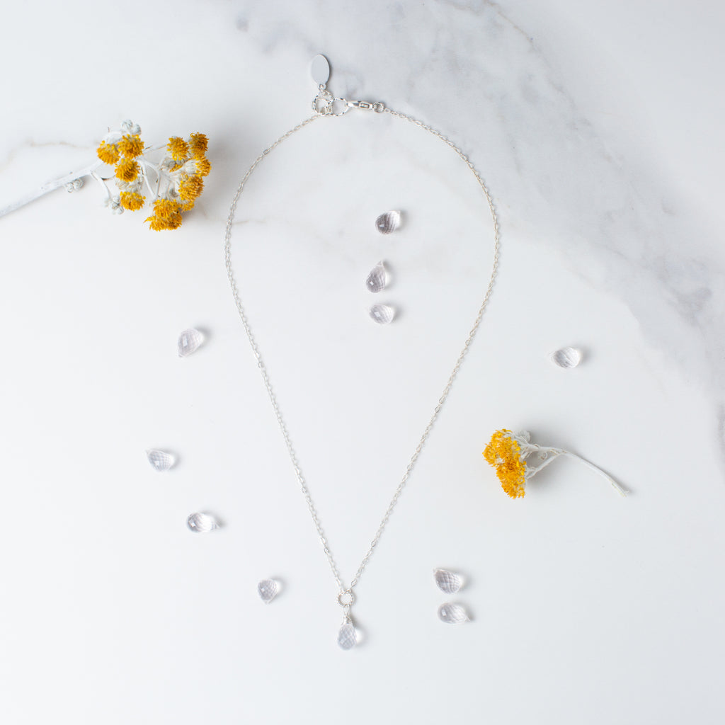 Teardrop-shaped Rose Quartz and Silver Necklace 'You Are Loved' Flay Lay with Yellow Flowers Photo by Asha Blooms