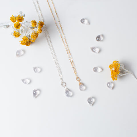 Teardrop-shaped Rose Quartz and Silver or Gold Necklace 'You Are Loved' Flat Lay with Yellow Flowers Photo by Asha Blooms