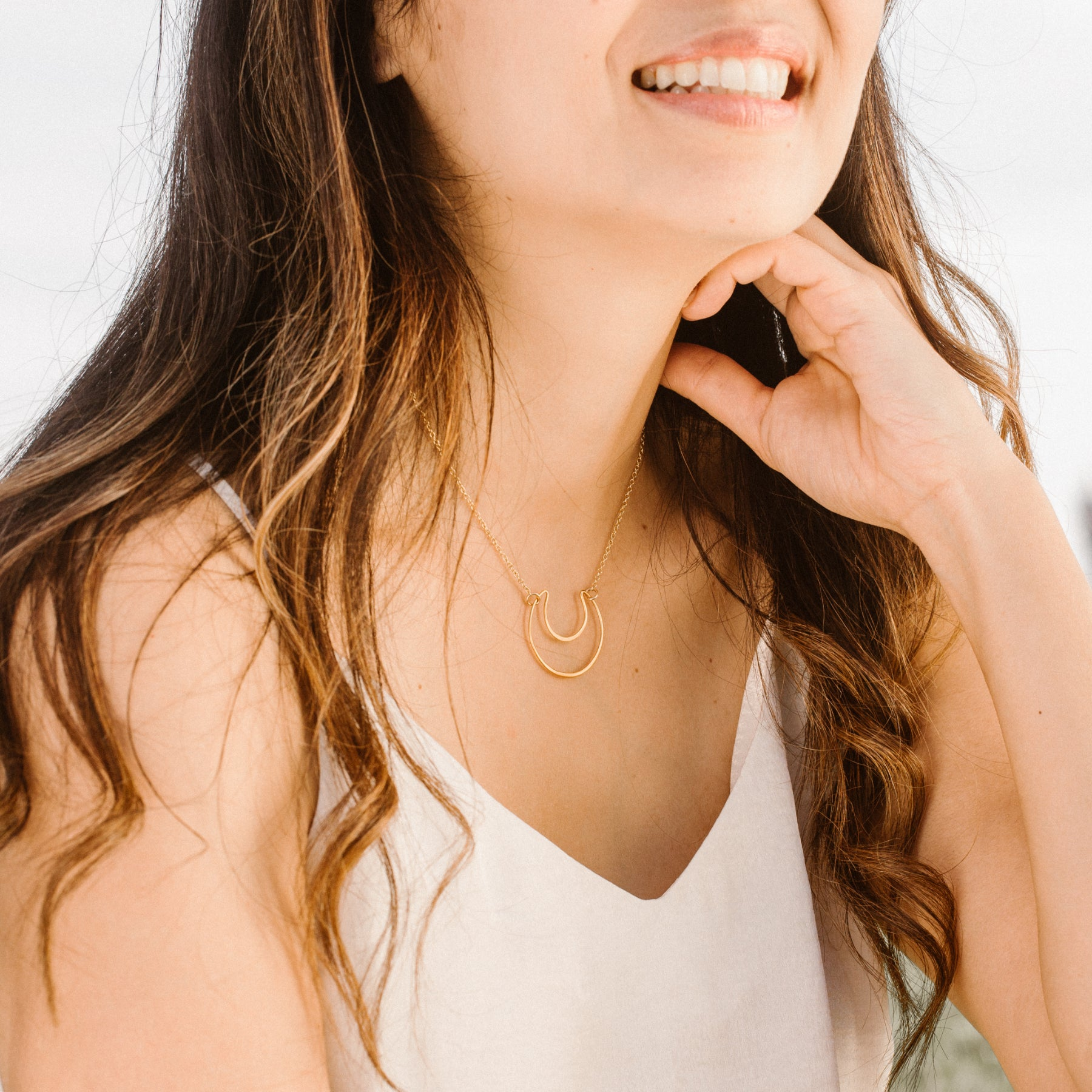 Woman in White Shirt Smiling and Wearing Gold Crescent Moon Pendant Necklace 'You Are Still Standing' Model Photo by Asha Blooms