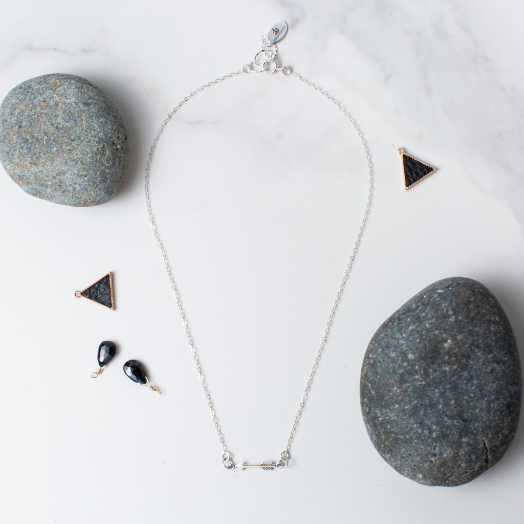 Silver Arrow Pendant Necklace 'You Are a Warrior' Flat Lay with Gray Stones and Beads Photo by Asha Blooms