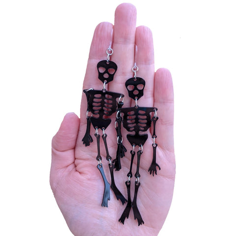 Exaggerated Skeleton Earrings (Dangles) - size comparison hand