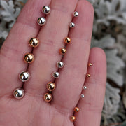Metallic Pearl Earrings (Studs) - size comparison hand