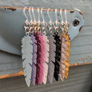 Dainty Feather Earrings Product Image of all color options resting on farm shutters