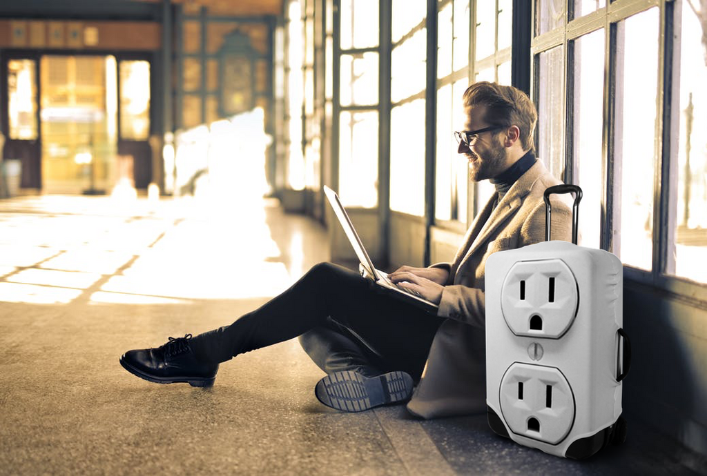 Man sits in airport terminal with outlet suitcase cover