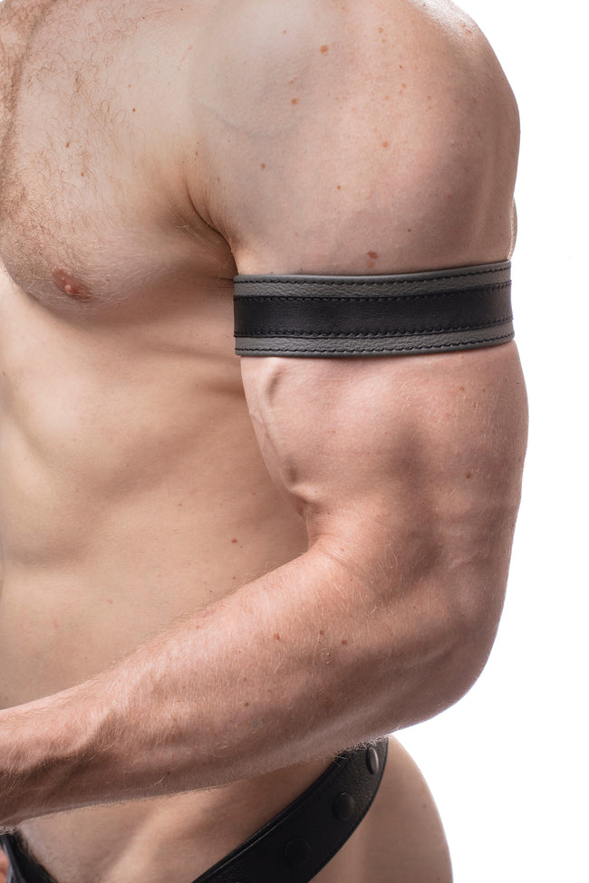 "Model wearing a 1.5"" grey leather armband with black racing stripe detail."