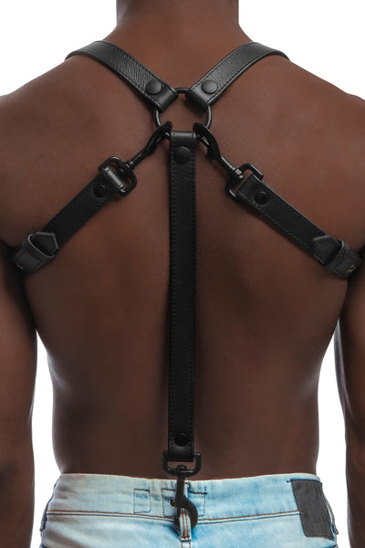 Model wearing black leather braces with black metal hardware as shoulder harness attached to jeans. Back 3.