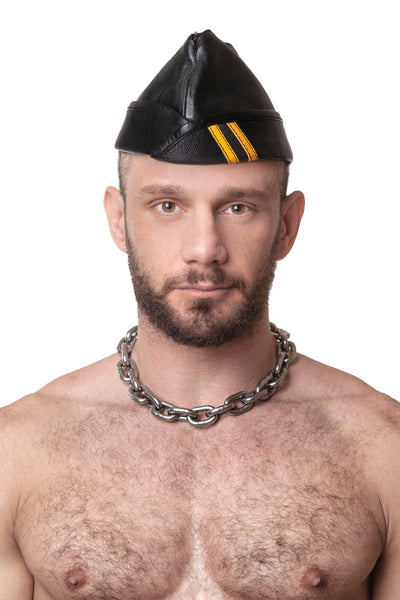 Model wearing black flight cap with yellow stripes