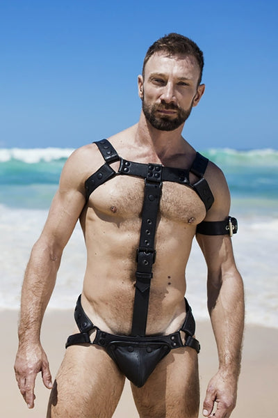 Model wearing black leather bulldog cockstrap with matt black metal hardware at the beach