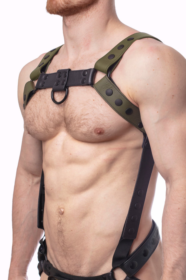 Model wearing an army green leather bulldog harness and connector with black hardware. Connector attached to a jockstrap. Side.
