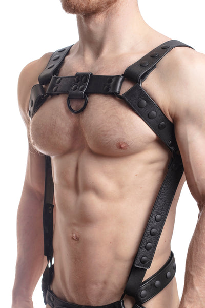 Model wearing a black leather bulldog harness and connector with black hardware. Connector attached to a jockstrap. Side.