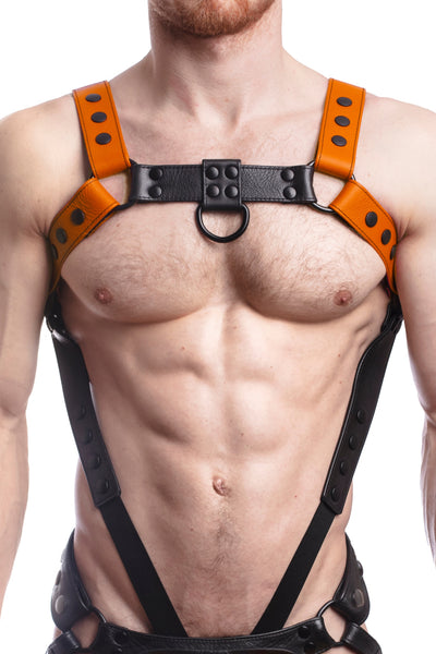 Model wearing an orange leather bulldog harness and connector with black hardware. Connector attached to a cockring. Front.