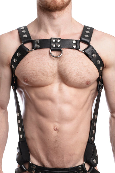 Model wearing a black leather bulldog harness and connector with stainless steel hardware. Connector attached to a jockstrap. Front.