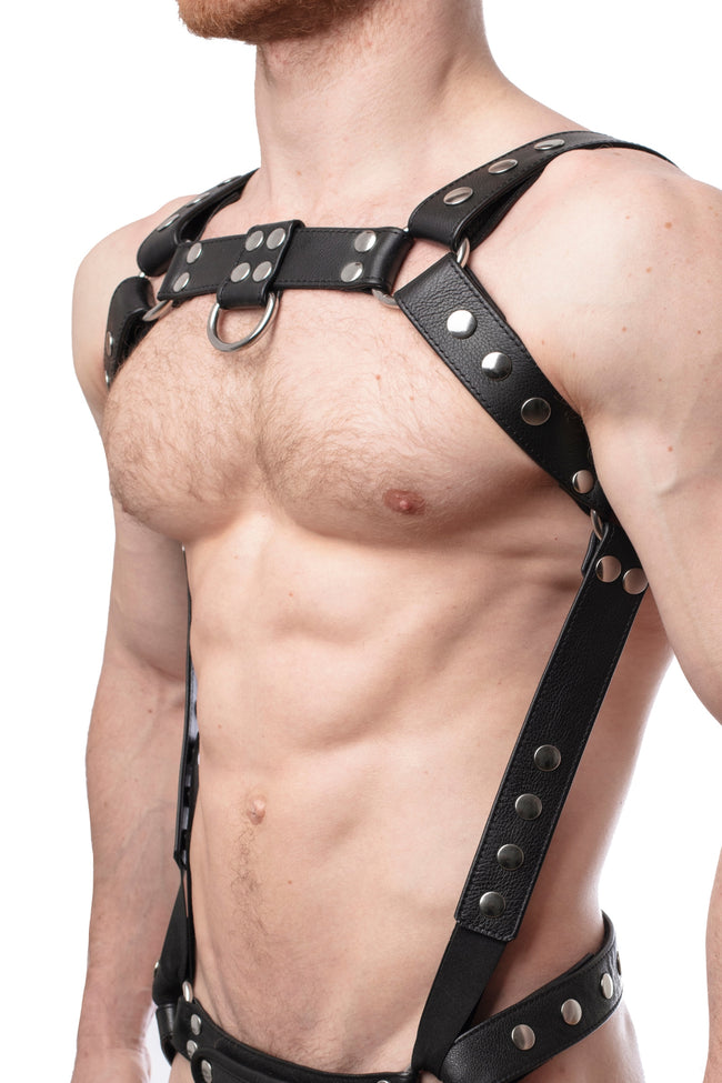 Model wearing a black leather bulldog harness and connector with stainless steel hardware. Connector attached to a jockstrap. Side.