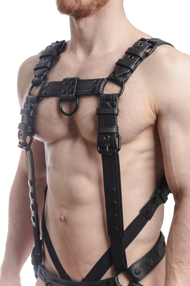 Model wearing a black leather combat harness and connector with black metal hardware. Side.