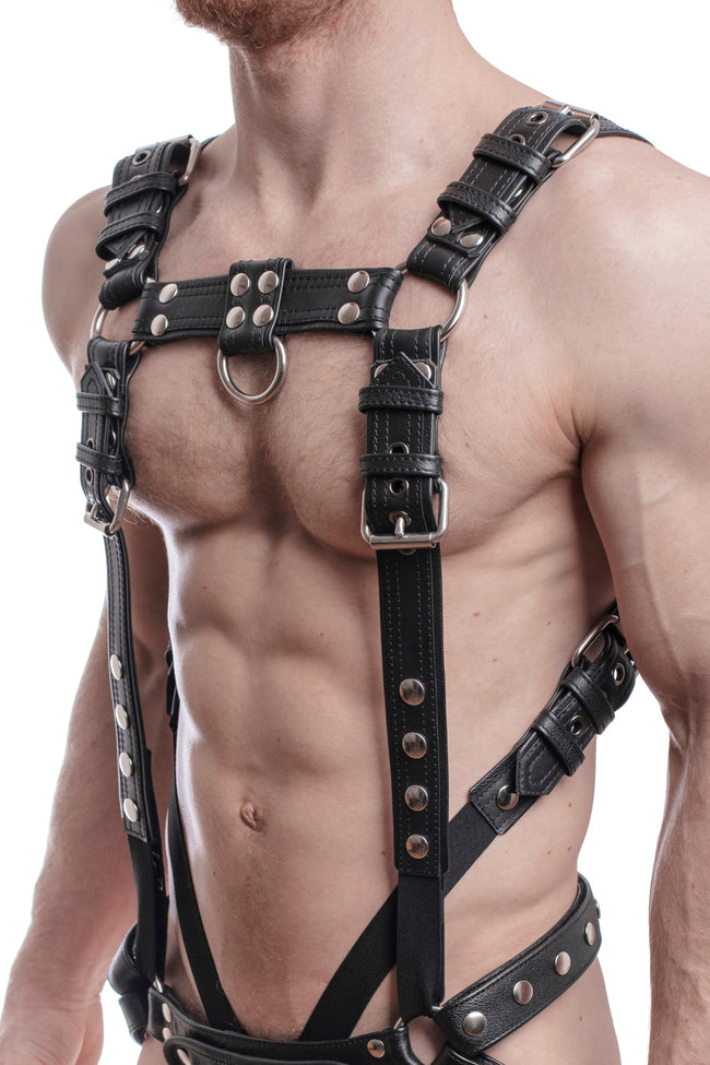 Model wearing a black leather combat harness and connector with stainless steel hardware. Side.