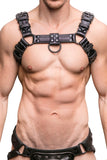 Model wearing a black leather combat harness with black metal hardware. Front.