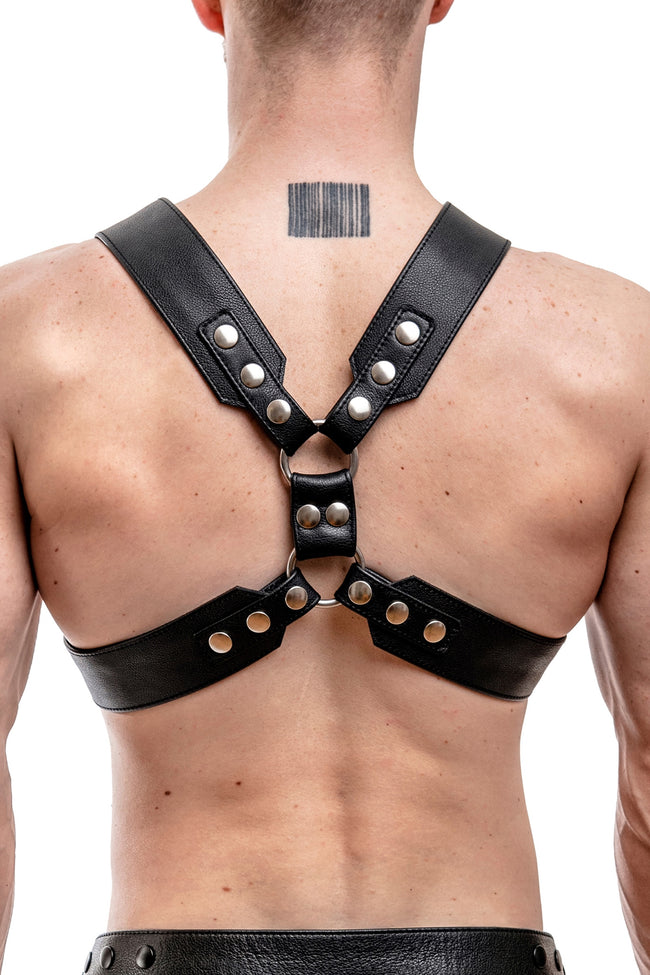 Model wearing a black leather commander harness with stainless steel hardware
