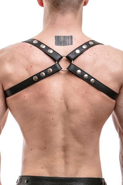 Model wearing black leather shoulder harness with stainless steel hardware
