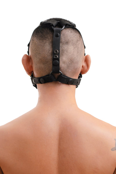Model wearing black leather head harness and muzzle back