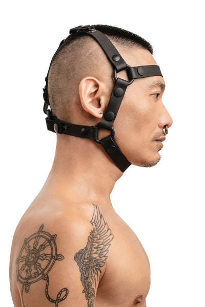 Model wearing black leather head harness side
