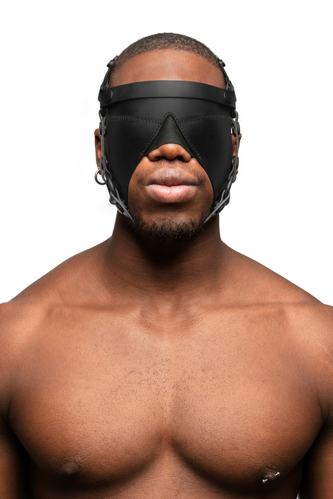 Model wearing black leather head harness and blinder with black metal hardware. Front view.