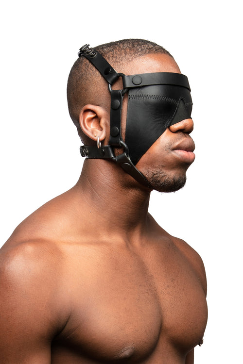 Model wearing black leather head harness and blinder with black metal hardware. Three quarter view.