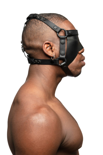 Model wearing black leather head harness and blinder with black metal hardware. Side view.