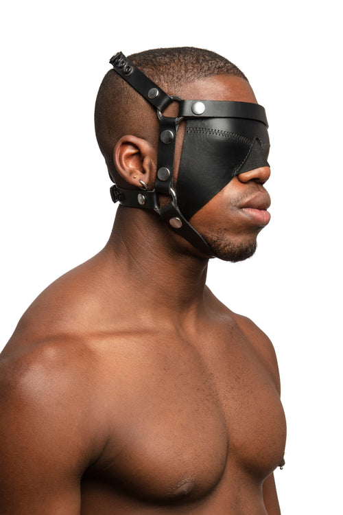 Model wearing black leather head harness and blinder with stainless steel hardware. Three quarter view.