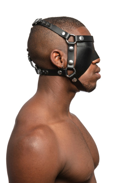 Model wearing black leather head harness and blinder with stainless steel hardware. Side view.