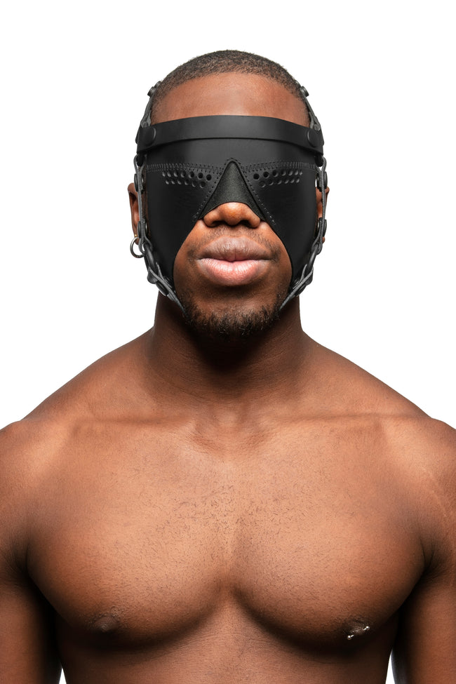 Model wearing black leather head harness and partial blinder with black metal hardware. Front view.