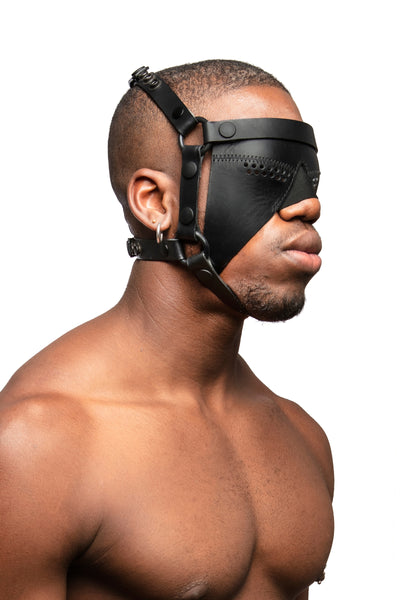 Model wearing black leather head harness and partial blinder with black metal hardware. Three quarter view.