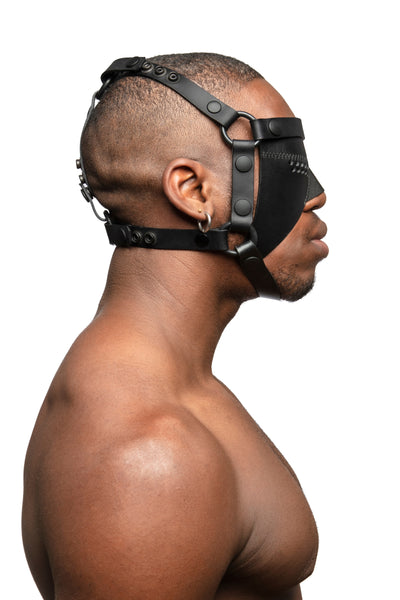 Model wearing black leather head harness and partial blinder with black metal hardware. Side view.