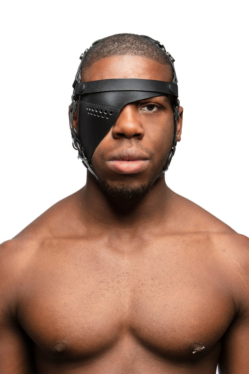 Model wearing black leather head harness and right eye patch with black metal hardware. Front view.