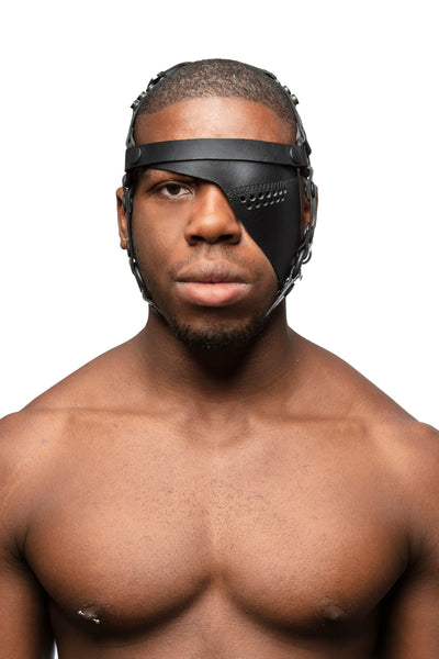 Model wearing black leather head harness and left eye patch with black metal hardware. Front view.