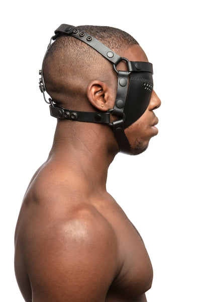 Model wearing black leather head harness and right eye patch with black metal hardware. Side view.