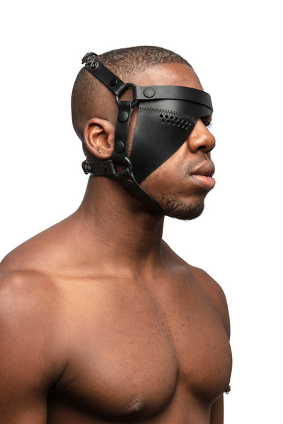 Model wearing black leather head harness and right eye patch with black metal hardware. Three quarter view.