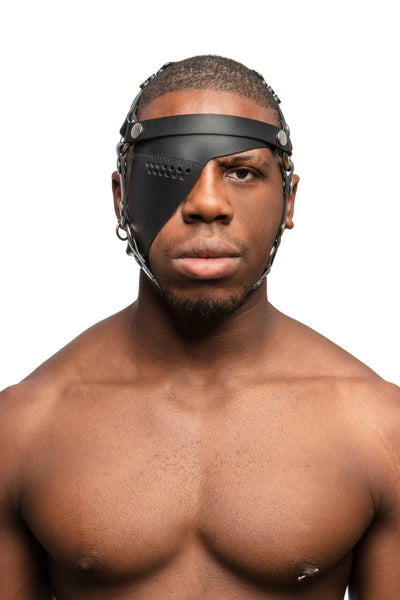 Model wearing black leather head harness and eye patch with stainless steel hardware. Front view.