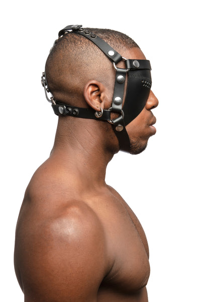Model wearing black leather head harness and eye patch with stainless steel hardware. Side view.