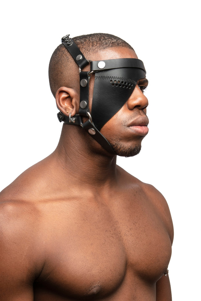 Model wearing black leather head harness and eye patch with stainless steel hardware. Three quarter view.